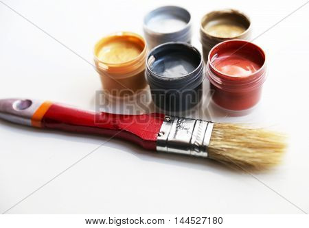 Set of colorful paints are located closed to red brush