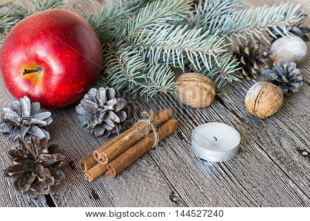 Preparation for Christmas. A branch of spruce, red apple, cinnamon sticks, candle, walnuts and cones on a gray wooden table. Selective focus.