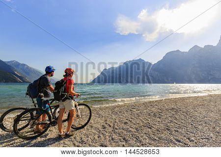 Mountain biking. Couple with bikes on Lake Garda, Riva del Garda, Italy.