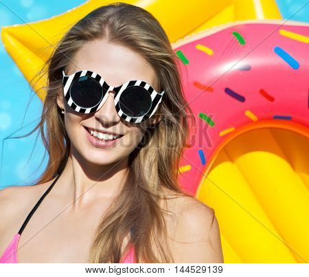 Summer beach style portrait a beautiful smiling happy young blonde woman wearing bikini and sunglasses with inflatable swimming pool toys