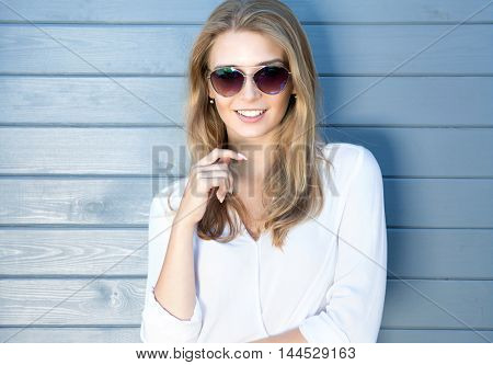 Portrait of beautiful young cheerful confident blonde woman with long hair wearing sunglasses and white shirt, wooden grey background behind her