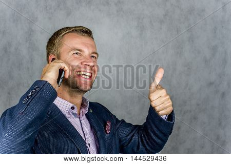 Businessman calling by phone and welcomes hand on a gray background