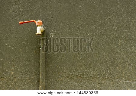 The Faucet on red on back dirty background