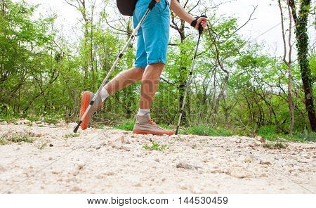 sporty young hiker walking through forest at summer