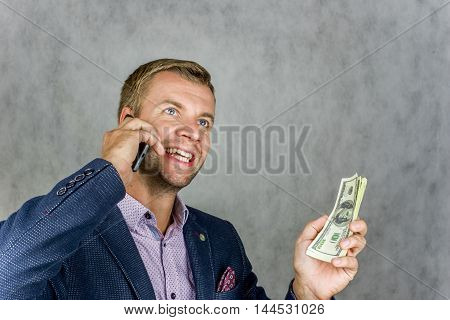 Businessman holding a money and phone and happily looking up at the gray background