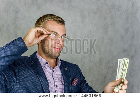 Businessman holding money and looking up thoughtfully in front of a gray background