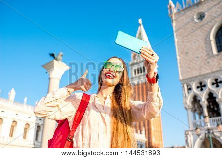 Young female traveler taking selfie photo on San Marco square in Venice. Happy Vacations in Venice
