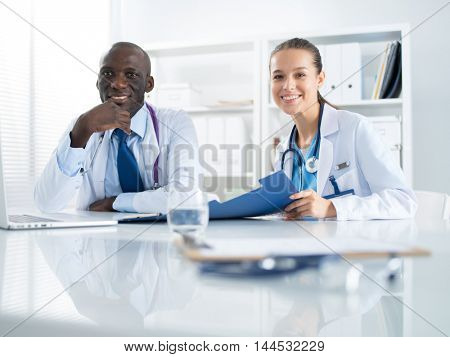 Two doctors working on an important folder in a medical office
