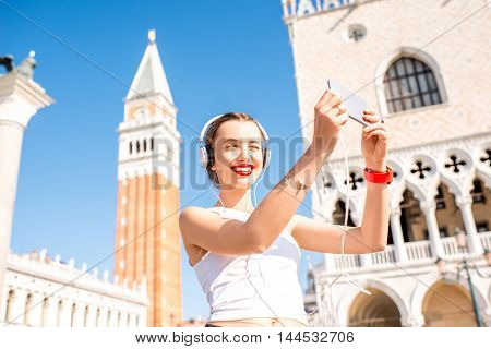 Young woman in sportswear taking selfie photo in front of Saint Marks tower in the center of Venice. Morning exercise in the old town of Venice