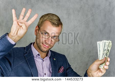 Businessman showing four fingers of his right hand, the left holds the money on a gray background