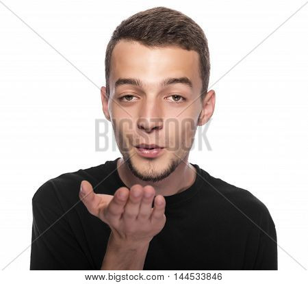 Young man sends a air kiss on a white background.