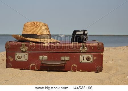 old suitcase,hat and a camera on the sea shore
