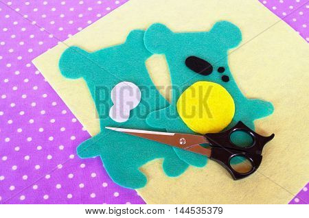 Homemade felt green animal kit, scissors on violet background with polka dots. Sewing project for children. Teddy bear patterns cut from felt. How to make a soft toy at home. Step-by-step