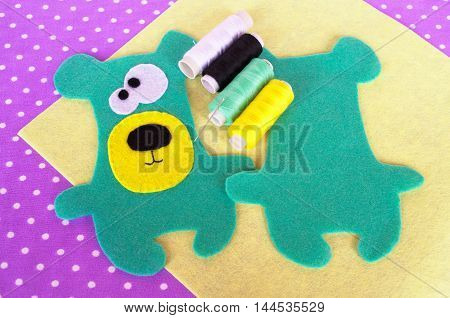Hand made felt green bear set on violet background with polka dots. How to sew a Teddy bear toy. Felt animal patterns. Sewing instructions for children. Step