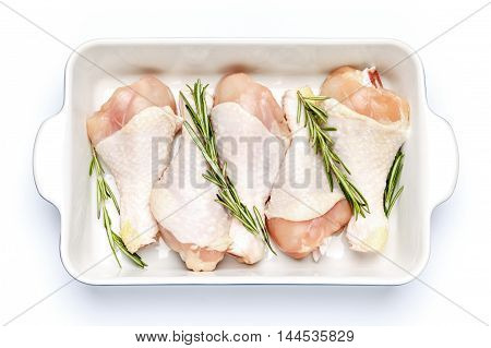 Raw chicken legs in baking dish isolated on a white background