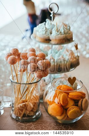 candy bar with yellow macaroons on table.