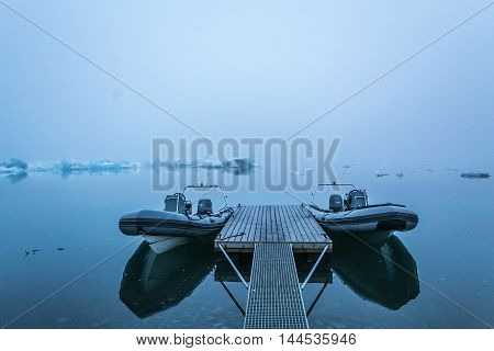 Two boat on pier ice background. Morning photo