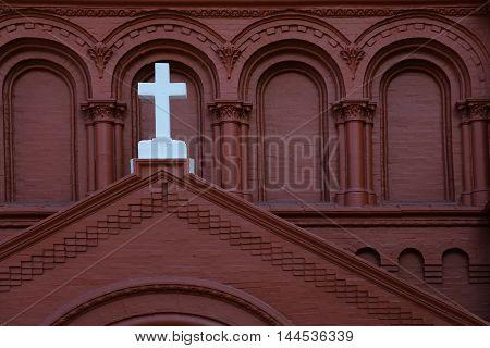 White church cross on red terrocota building