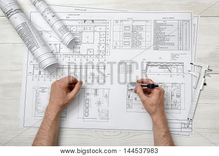 Close-up hands of man holding an engineering divider over drawing plan in top view. Engineering work. Measurement.