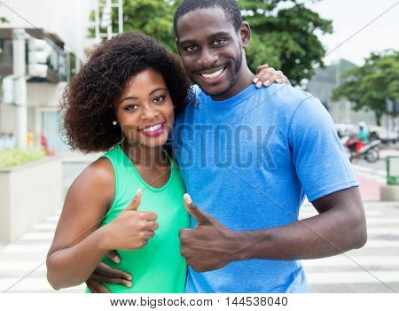 African american couple showing thumb up in the city