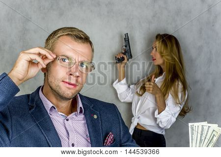 Businessman holding money and looking away in the background beautiful girl with a gun on a gray background