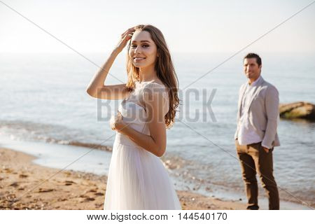 Portrait of a beautiful married couple standing at the beach