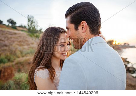 Close up portrait of a beautiful married couple laughing at the beach