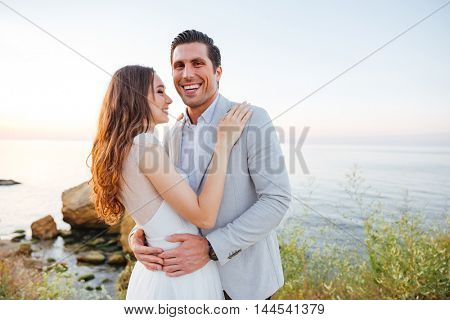 Romantic married couple standing and laughing on the beach at sunset