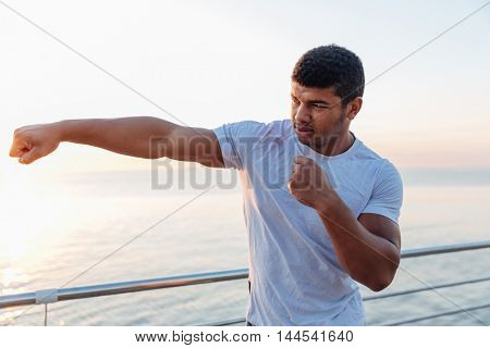 Muscular african american young sportsman standing and doing exercises outdoors