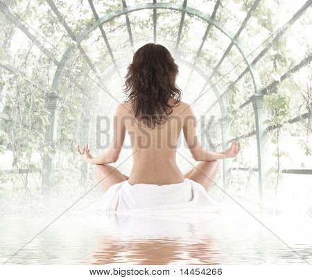 Young fit brunette meditating in the garden