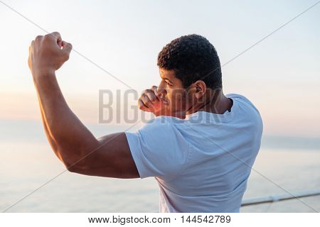 Muscular african american young man athlete standing and practicing shadow boxing outdoors