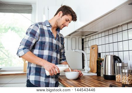 Attractive young man in plaid shirt standing and pouring milk into bowl for breakfast on the kitchen