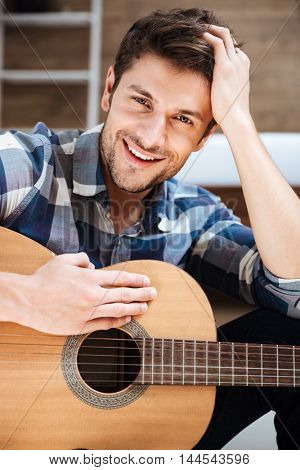 Happy handsome young man in plaid shirt holding guitar