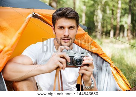 Portrait of handsome young man with vintage photo camera sitting in touristic tent in forest