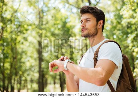 Thoughtful young man with backpack thinking and looking at watch in forest