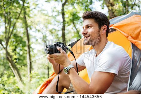 Happy young man tourist sitting and using modern photo camera in forest