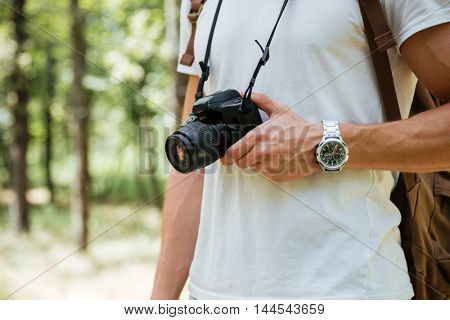 Closeup of young man photographer holding modern photo camera in forest