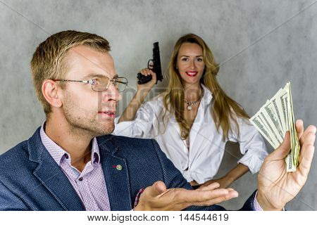 Businessman holding money and looking at them in the background beautiful girl with a gun on a gray background