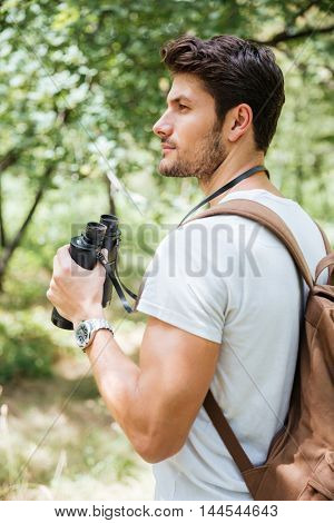 Pensive young man with backpack holding binoculars and thinking in forest