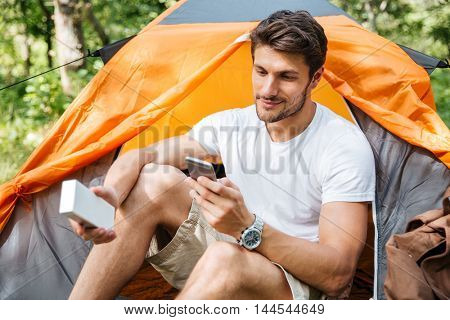 Handsome young man tourist using cell phone and portable mini speaker in touristic tent