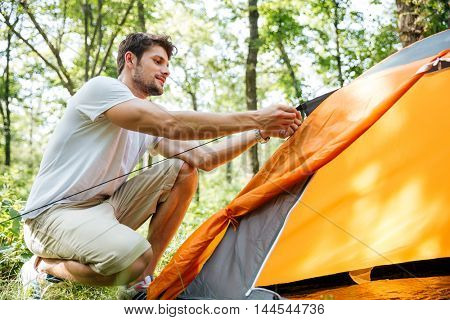 Handsome young man tourist setting up touristic tent in forest