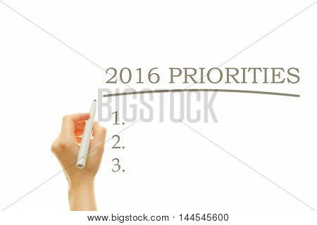 Woman hand writing 2016 PRIORITIES List on a transparent wipe board
