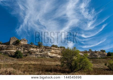 autumn landscape ruined ancient walls on a hill against the blue sky in Crimea.