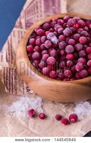 Close up of frozen cranberries. Healthy frozen berries in wooden bowl on old newspaper.