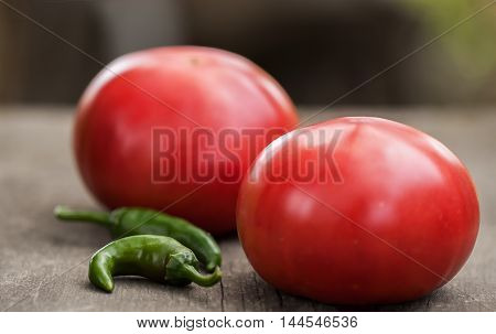 Two fresh home-grown tomatoes and spicy green chili peppers on a rustic wooden kitchen table. Two commonly encountered ingredient in many dishes and sauces.