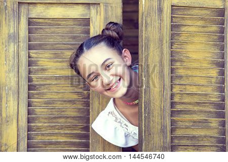 girl looks out from behind a wooden door