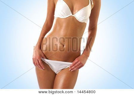 Belly of beautiful young female sportsman over blue background