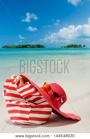 Summer beach bag with red  straw hat and sunglasses on sandy beach