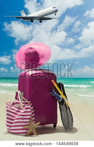 Suitcase and big straw hat on the beautiful beach