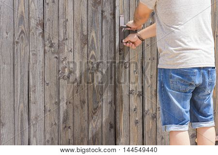 a person opens an old wooden door with a key